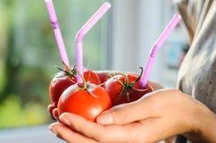 3 зрелых красных томата с соломами в руках Стоковые Изображения RF