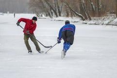 2 зрелых люд воюя для шайбы пока игра hokey на замороженном реке Dnipro в Украине стоковая фотография