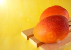 2 зрелых манго на деревянных досках на яркой желтой предпосылке Стоковые Изображения RF