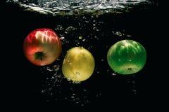 3 зрелых разнообразия яблок понижаются в воду Стоковые Изображения RF