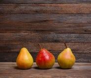 3 зрелых сладостных груши на старой деревянной ретро предпосылке Стоковое Фото