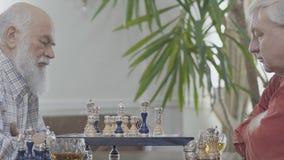 2 зрелых старших друз играя усаживание шахмат дома Кавказские соседи стариков играя шахматы joyfully внутри помещения видеоматериал
