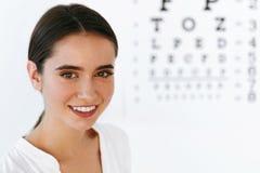 зрение Красивая женщина с визуальной диаграммой испытания глаза на предпосылке Стоковые Изображения