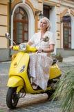 Зрелая дама на желтом самокате стоковая фотография