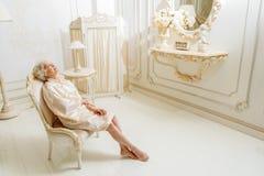 Зрелая дама отдыхая в ее шикарной квартире стоковые фото