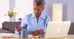 Зрелая африканская женщина оплачивая ее счеты Стоковые Изображения