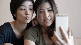 Зрелая взрослая азиатская женщина 2 принимая фото, selfie используя pho клетки Стоковое Изображение
