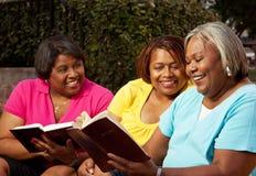 Зрелая группа в составе женщины говоря и читая стоковые фото