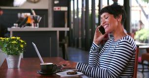 Зрелая женщина в кафе работая на компьтер-книжке и отвечая телефоне акции видеоматериалы