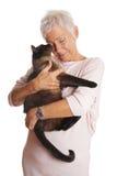 Зрелая женщина держа кота в ее оружиях Стоковое Изображение