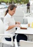 Зрелая женщина есть на таблице в кафе Стоковая Фотография