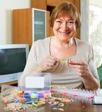 Зрелая женщина делает браслеты дома Стоковое фото RF