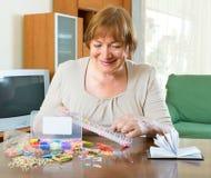 Зрелая женщина делает браслеты дома Стоковое Изображение