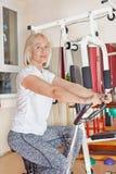 Зрелая женщина делая тренировку на велосипеде стоковые изображения rf