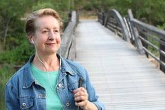 Зрелая женщина используя умный телефон outdoors стоковое изображение