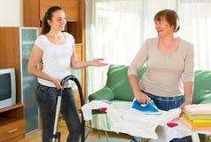 Зрелая женщина и девушка очищая дома стоковое фото