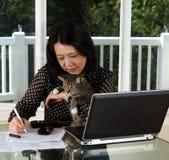 Зрелая женщина и ее кот любимчика работая дома Стоковые Фотографии RF