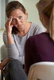 Зрелая женщина обсуждая проблемы с советником Стоковая Фотография
