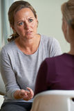 Зрелая женщина обсуждая проблемы с советником Стоковые Фотографии RF