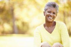 Зрелая женщина ослабляя в ландшафте осени Стоковое фото RF