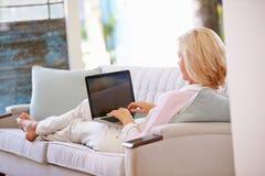 Зрелая женщина ослабляя на софе дома используя портативный компьютер Стоковые Изображения RF