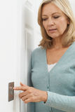 Зрелая женщина поворачивая выключатель дома Стоковое Изображение RF