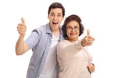 Зрелая женщина при ее внук держа их большие пальцы руки вверх Стоковые Фотографии RF