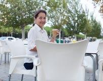 Зрелая женщина сидя на таблице в кафе Стоковое Фото