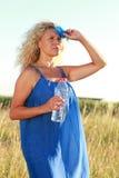 Зрелая женщина с бутылкой с водой в лете стоковая фотография rf