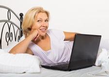 Зрелая женщина с компьтер-книжкой в кровати Стоковое фото RF
