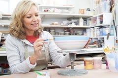 Зрелая женщина украшая шар в классе гончарни стоковые фотографии rf
