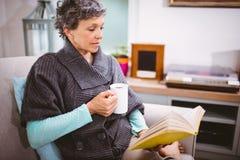Зрелая кружка книги чтения женщины и кофе удерживания Стоковое Изображение