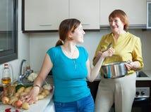Зрелая дочь женщины и взрослого варя еду Стоковое Фото
