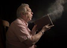 Зрелая пылевая поземка человека с старой книги Стоковая Фотография