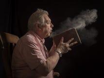Зрелая пылевая поземка человека с старой книги Стоковое фото RF