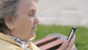 Зрелая старуха говоря на мобильном телефоне outdoors видеоматериал