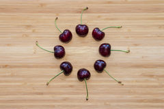 Зрелая темнота - красные вишни в круге на деревянной доске Стоковые Фотографии RF