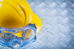 Зрелища безопасности строя шлем на рифлёной металлопластинчатой верхней части Стоковые Изображения