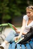 Зрелища девушки и с таблеткой в руке принимают усаживание книги Стоковое Фото