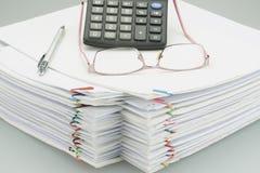 Зрелища и ручка на куче белой бумаги перегрузки Стоковое Фото