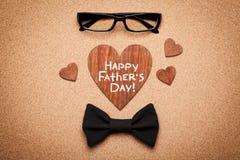 Зрелища, bowtie и деревянное сердце с днем отцов примечания счастливым, предпосылкой пробковой доски, взгляд сверху, плоским поло Стоковые Изображения