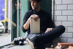 Зрелое предприниматель дела в черной рубашке сидя внутри помещения внутреннее и наслаждаясь хорошим днем Стоковая Фотография