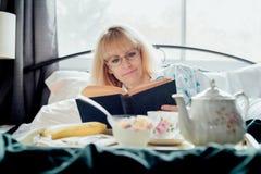 Зрелое чтение женщины имея завтрак в кровати Стоковые Фотографии RF