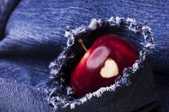 Зрелое яблоко с сердцем на джинсах предпосылке, конце-вверх Здоровый съешьте Стоковое фото RF