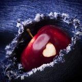 Зрелое яблоко с сердцем на джинсах предпосылке, конце-вверх Здоровый съешьте Стоковые Фотографии RF