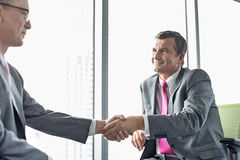 Зрелые бизнесмены тряся руки в офисе Стоковое Фото