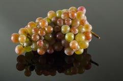 Зрелые виноградины на черном зеркале Стоковые Фото