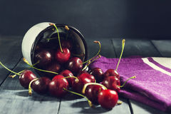 Зрелые вишни в железной кружке на синей деревянной предпосылке Стоковые Фото