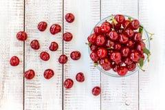 Зрелые вишни в шаре на белой деревянной предпосылке Стоковая Фотография