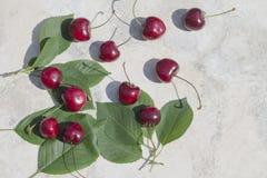 Зрелые вишни с зелеными листьями на светлой предпосылке Стоковые Изображения RF